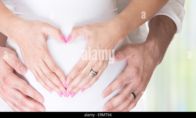 Schwangere Frau und ihr Mann Hand in Hand auf Bauch in Herzform, jungen Liebenden Familie, neues Leben Konzept Hintergrund Stockbild