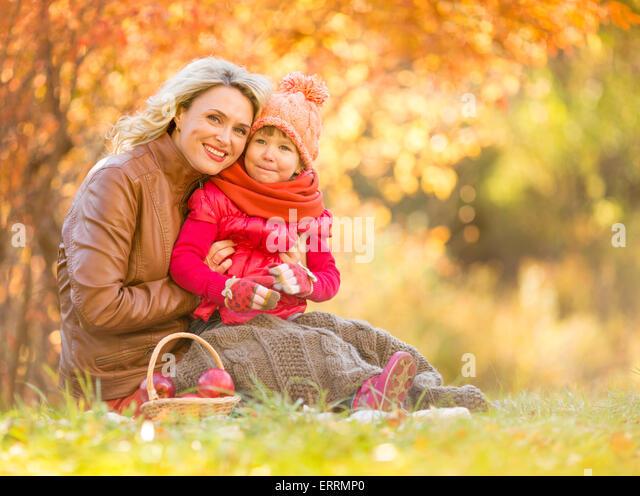 Glückliche Mutter und Kind sitzt im Freien im Herbst Stockbild
