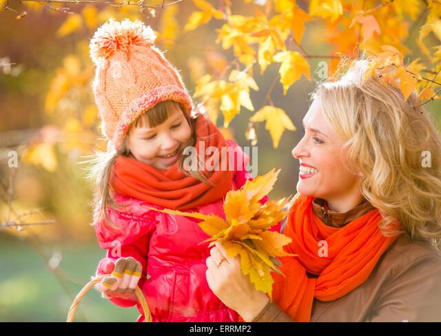Lächelnde Mutter und Kind im Freien mit gelben Blätter im Herbst Stockbild