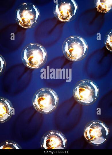 Eine Gruppe von beleuchteten Glühlampen Leuchten auf blauem Hintergrund Stockbild