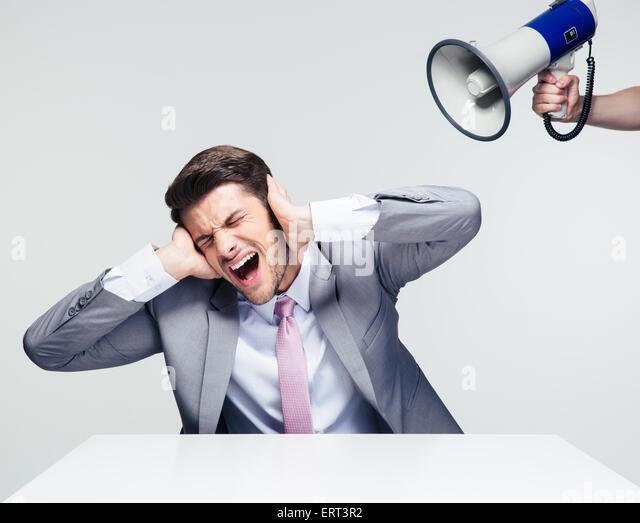 Geschäftsmann am Tisch sitzen und für die Ohren von Megaphon auf grauem Hintergrund Stockbild