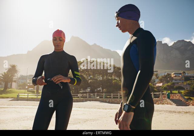 Aufnahme des jungen Mann und Frau mit ihren Badesachen im stehen am Strand. Triathleten, die Vorbereitung für Stockbild
