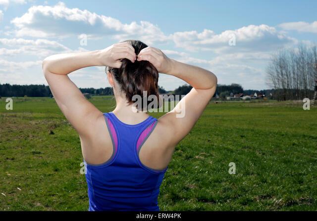 Rückseite der jungen Frau auf der grünen Wiese Befestigung ihren Pferdeschwanz Stockbild