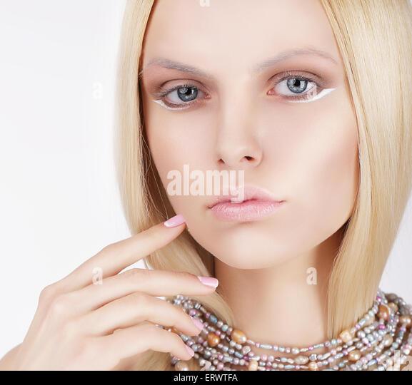 Anspruchsvolle schöne Blondine, die ihr Gesicht zu berühren Stockbild