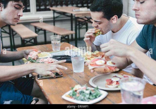 Freunde, die Mahlzeit in öffentliche Sitzgelegenheiten im Freien im New Yorker Finanzviertel Stockbild