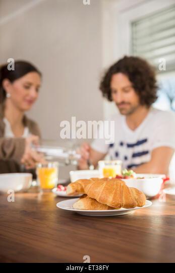 Croissants am Esstisch und Mitte erwachsenes paar frühstücken im Hintergrund, München, Bayern, Deutschland Stockbild