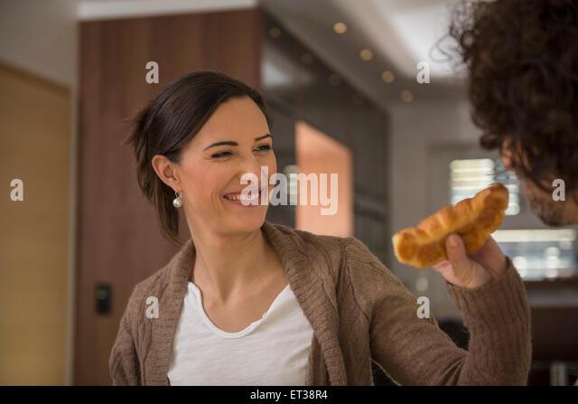 Zarte Frauenhand Fütterung eine Croissant zu ihrem Mann, München, Bayern, Deutschland Stockbild