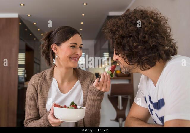 Mitte Erwachsene Frau Fütterung eine Erdbeere zu ihrem Mann, München, Bayern, Deutschland Stockbild