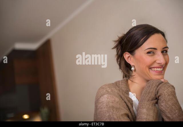 Nahaufnahme einer Mitte erwachsenen Frau lächelnd mit stützte sich auf Ellenbogen, München, Bayern, Stockbild
