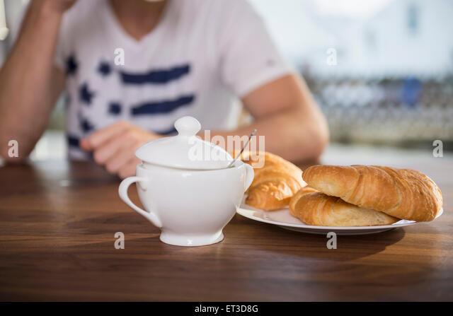 Mann sitzt am Frühstückstisch, München, Bayern, Deutschland Stockbild