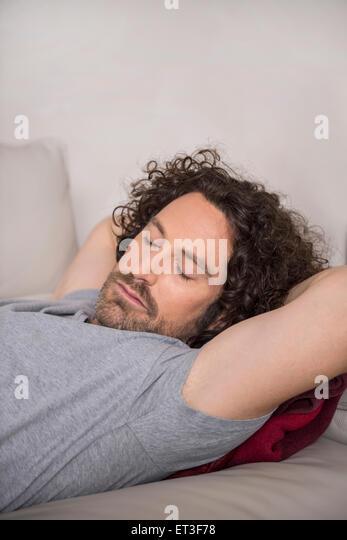 Mitte erwachsenen Mannes auf Schlafcouch, München, Bayern, Deutschland Stockbild