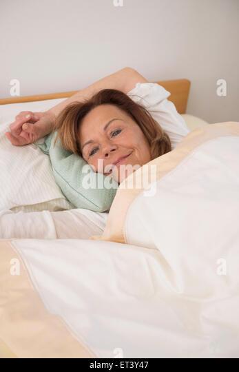 Ältere Frau schläft auf Bett in ihrem Schlafzimmer zu Hause, München, Bayern, Deutschland Stockbild