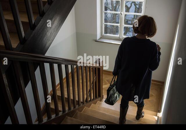 Rückansicht des senior Trägerin Wintermantel nach unten bewegen, auf einer Treppe, München, Bayern, Stockbild