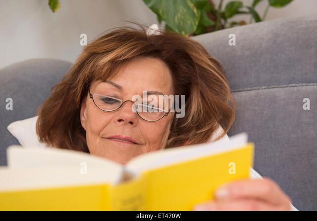 Ältere Frau liest ein Buch liegend auf dem Sofa zu Hause, Munich, Bavaria, Germany Stockbild