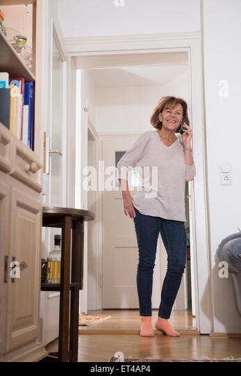 Ältere Frau am Handy an Tür, München, Bayern, Deutschland Stockbild
