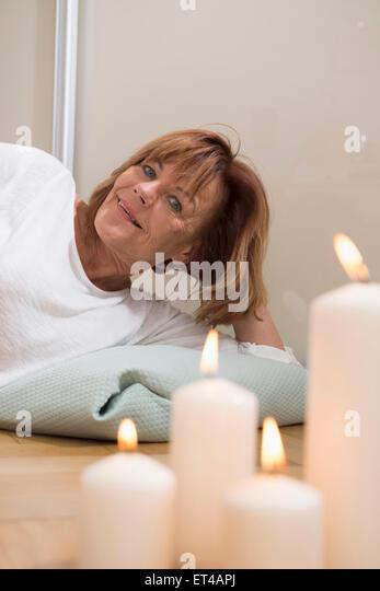 Ältere Frau mit Kissen auf dem Boden liegend brennende Kerzen im Vordergrund, München, Bayern, Deutschland Stockbild