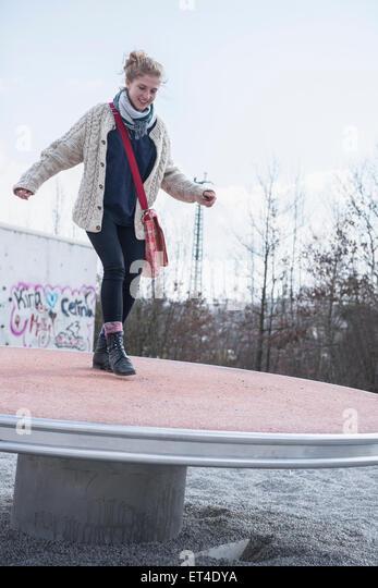 Junge Frau balancieren auf Spielplatz Spinner München Bayern Deutschland Stockbild
