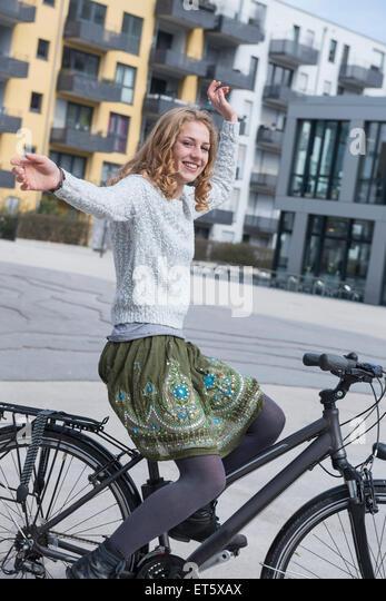 Junge Frau, die Durchführung von Stunt mit dem Fahrrad, München, Bayern, Deutschland Stockbild