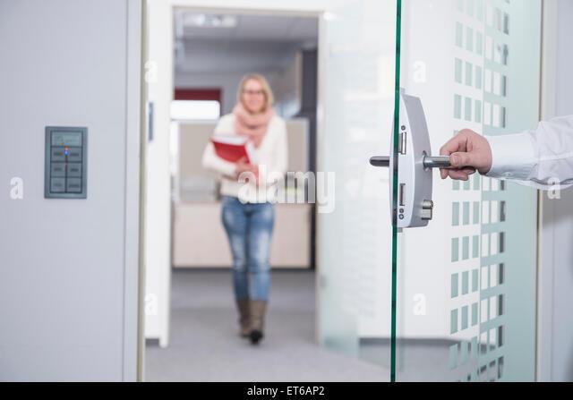 Geschäftsmann, öffnen der Bürotür für seinen Kollegen, München, Bayern, Deutschland Stockbild