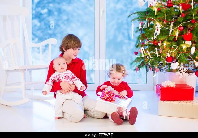 Drei Kinder öffnen Weihnachtsgeschenke, Weihnachten Morgen in ein Wohnzimmer mit geschmückten Baum und Stockbild