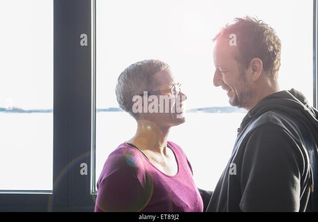 Seitenansicht eines Paares einander betrachtend und lächelnd, Bayern, Deutschland Stockbild