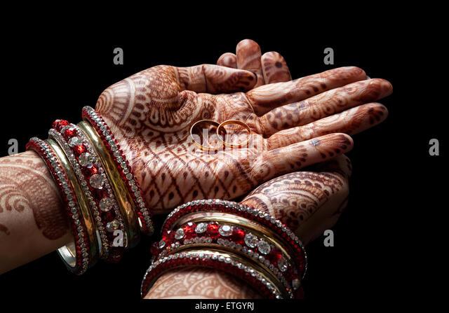 Frau Hände mit Henna halten zwei goldene Hochzeit Ringe auf schwarzem Hintergrund Stockbild