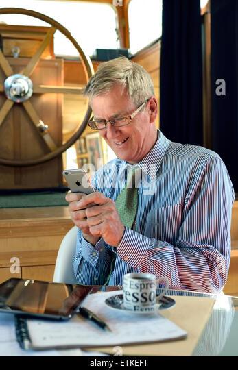 Lächelnd Unternehmer Geschäftsmann SMS mit seinem iPhone 6 Smartphone sitzen in seinem Hausboot Hausboot Stockbild