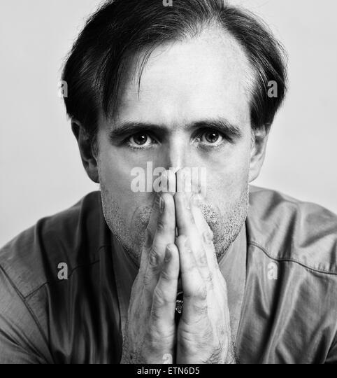Close-up Portrait eines Mitte erwachsenen Mannes mit seinen Händen vor dem Mund Stockbild