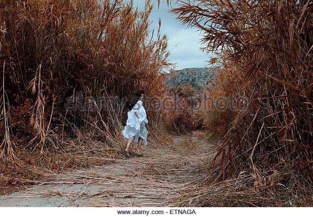 Frau läuft auf einem Pfad über die Schulter schauen Stockbild