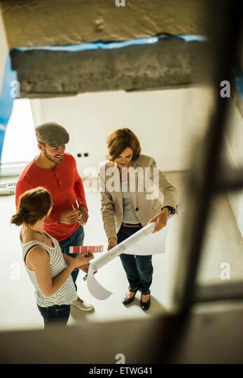 Architekt und junge Paar diskutieren Farbmuster und Bau planen Stockbild
