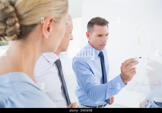 Geschäftsmann, Zeichnen von Graphen auf dem Brett Stockbild