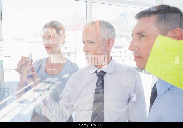 Geschäftsmann, Zeichnen von Graphen auf dem Glas Stockbild