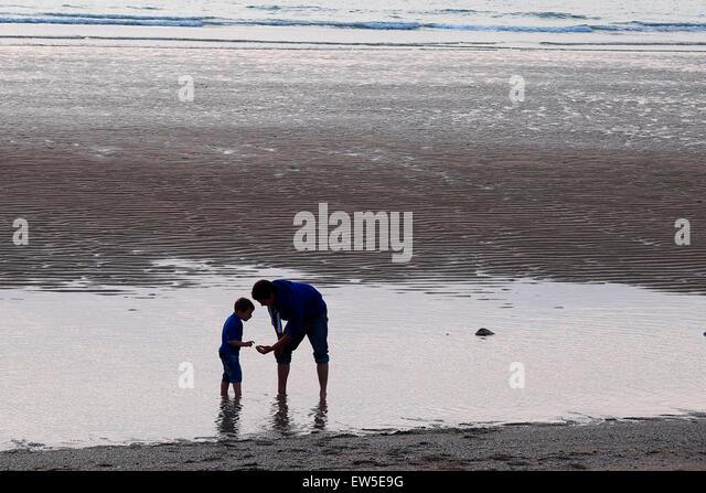 Vater und Sohn die Erkundung auf den Fistral Beach in Newquay, Cornwall. Stockbild
