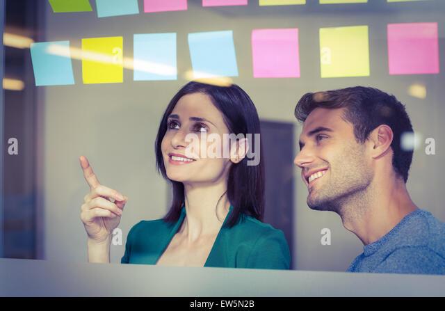 Kollegen betrachten Haftnotizen Stockbild