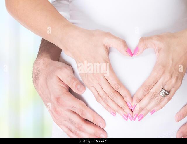 Nahaufnahme Foto schwangere Frau und ihr Mann Hand in Hand auf den Bauch in Herzform, glückliche und gesunde Stockbild