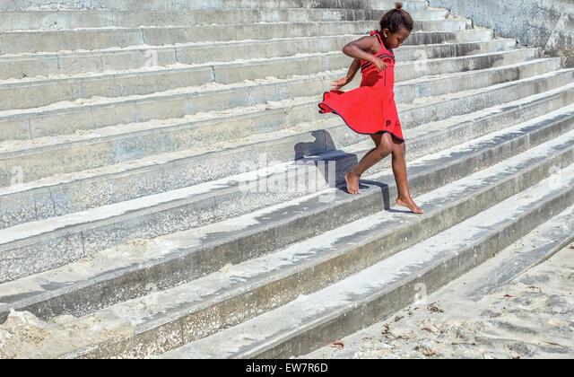 Mädchen in einem roten Kleid, die Treppe hinunter laufen Stockbild