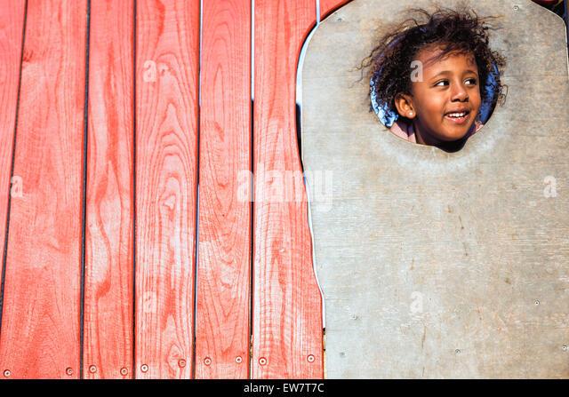 Lächelndes Mädchen stossen ihren Kopf durch ein Loch in der Wand, Perth, Australien Stockbild