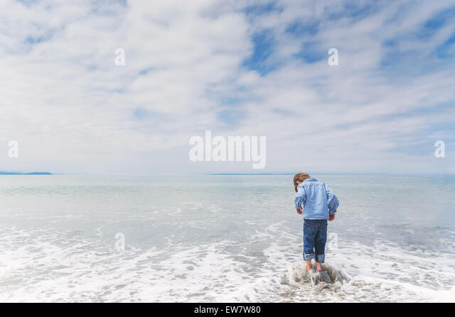 Rückansicht eines jungen auf einem Felsen im Meer Stockbild
