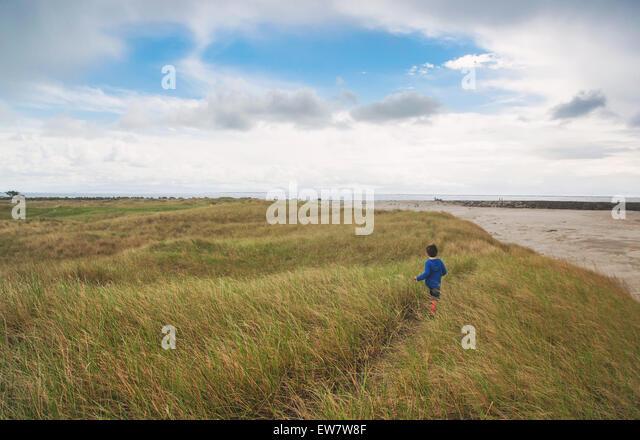 Junge läuft durch Rasen am Strand Stockbild