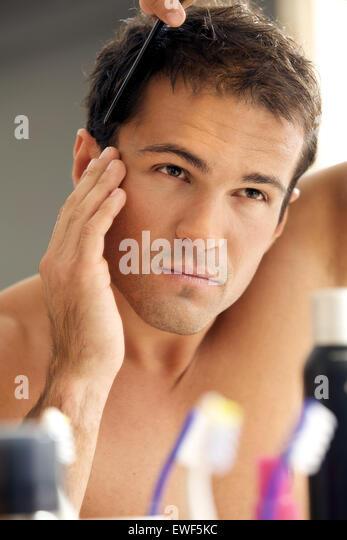Junger Mann seine Haare kämmen Stockbild