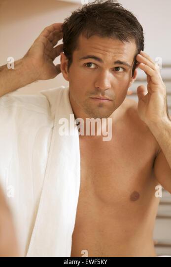 Junger Mann in Spiegel Stockbild