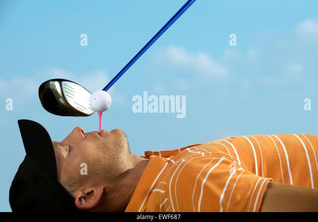 Mann Ausgleich Golfball am Abschlag in den Mund Stockbild