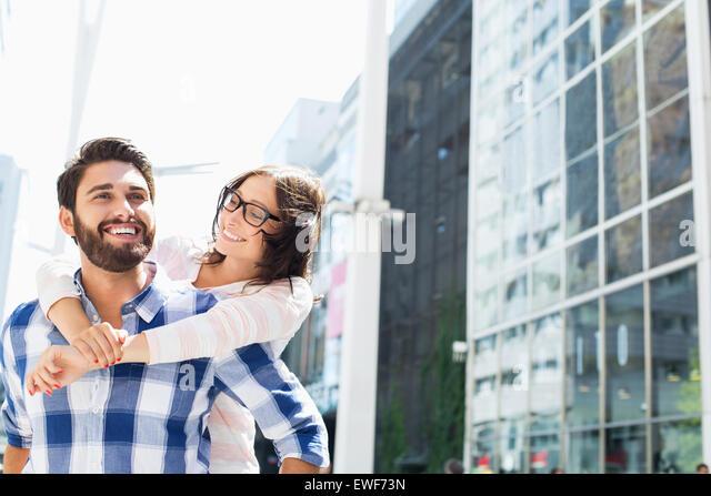 Glücklicher Mann geben Huckepack Fahrt zur Frau in der Stadt Stockbild