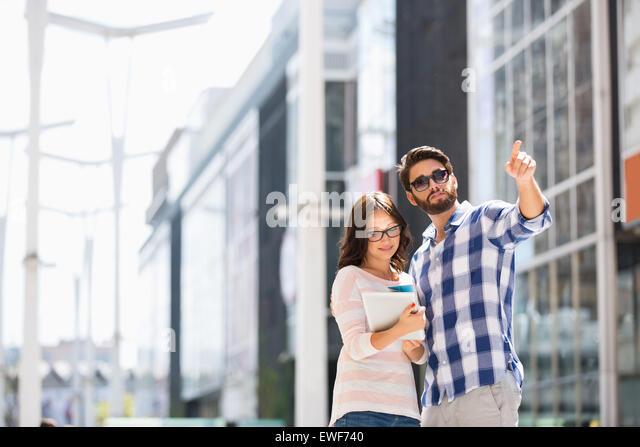 Mann und Frau mit digital-Tablette vor Gebäude zeigte Stockbild