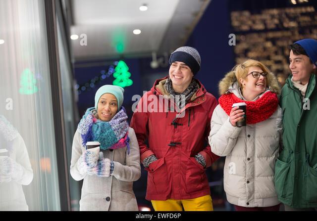 Glücklich multiethnischen Freunde im Winter tragen zu Fuß in die Stadt während der Dämmerung Stockbild