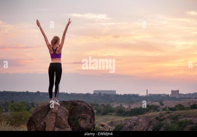 Junge sportliche Frau mit Armen hob bei Sonnenuntergang im Sommer Stockbild