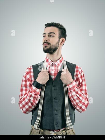 Entsättigt Porträt stehen junge Hipster Modell Wegsehen mit angehobenen Augenbraue halten Sie seine Hosen Stockbild