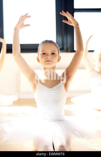 Zierliche hübsche kleine Ballerina mit erhobenen Armen in ihrem weißen tutu in einem hellen, sonnendurchfluteten Stockbild