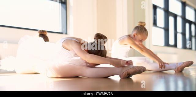 Wenig Ballett Mädchen tun eine Dehnung warm up Übung im Studio vor ihren Tanz. Stockbild