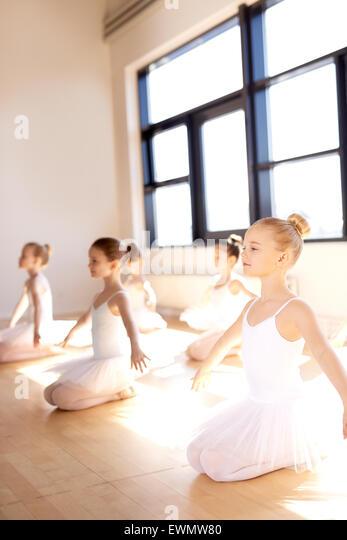 Hübsche kleine Ballett Mädchen sitzen auf ihren Knöcheln mit offenen Armen für Stretching Übung Stockbild